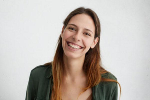 Женщина в зеленой кофте улыбается