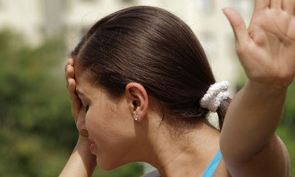 Женщина прячет свое лицо, выставляет руку вперед, чтоб ее не трогали