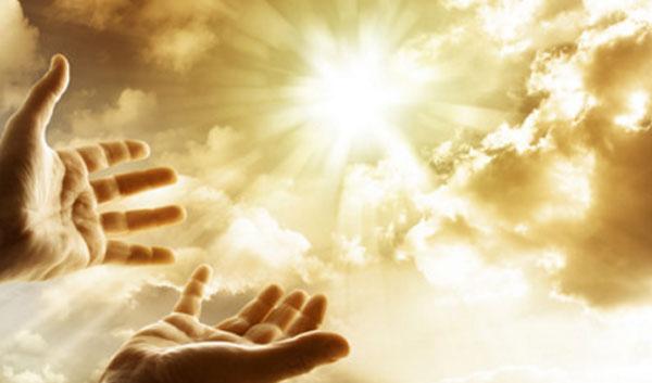 Руки человека тянутся к небу, на котором раздвинулись тучи и вышло солнце