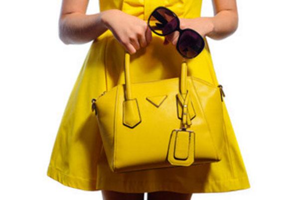 Девушка в желтом платье с желтой сумочкой и солнцезащитными очками в руке