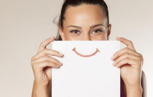 Улыбающаяся девушка прикрывает свои губы рисунком улыбки