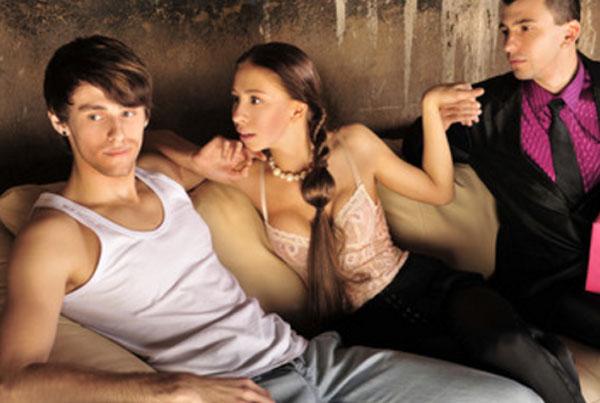 На диване два парня и девушка, которая засматривается на парня, который смотрит в другую сторону