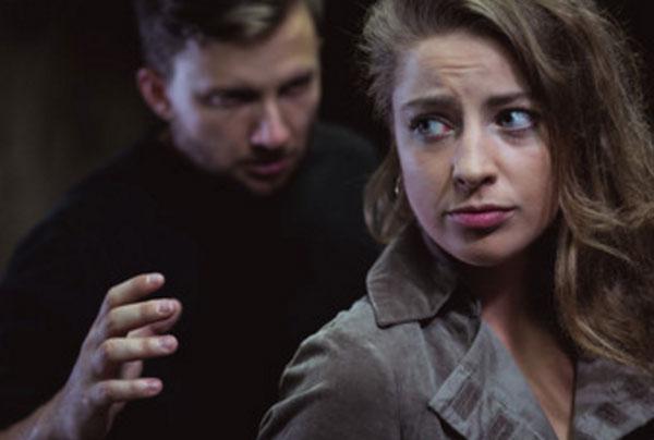 Мужчина стоит сзади слегка испуганной женщины