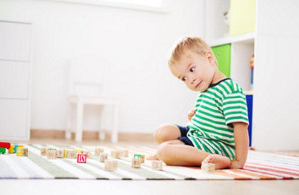 Мальчик сидит на полу, смотрит на кубики