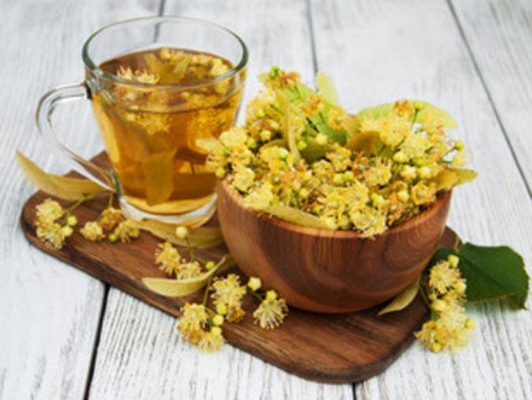 На досточке стоит чашка с липовым чаем и миска с соцветиями