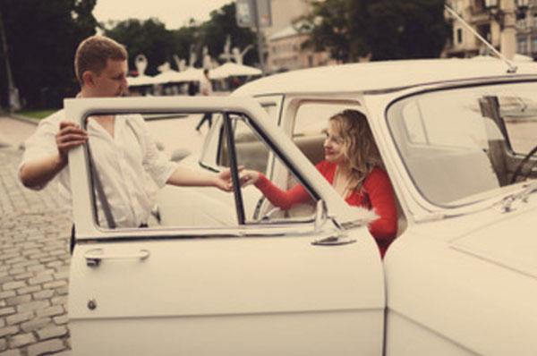 Мужчина открыл дверцу машины, подает женщине руку, чтоб она смогла выйти