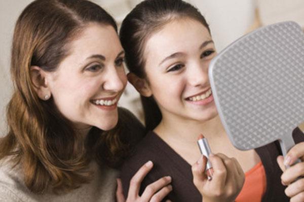 Мама с дочерью смотрятся в зеркало. У девочки в руке губная помада