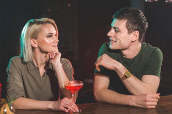 Парень говорит что-то девушке, которая сидит рядом за барной стойкой. У нее бокал с алкогольным напитком