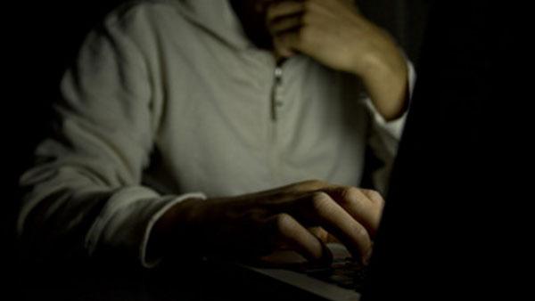 Мужчина в темноте сидит перед ноутбуком