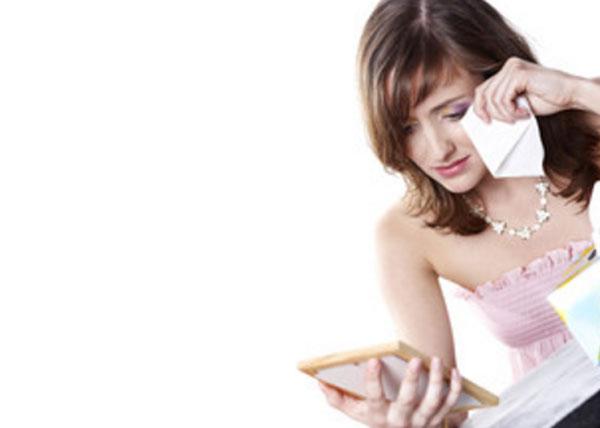 Женщина плачет, глядя на фотографию в рамке