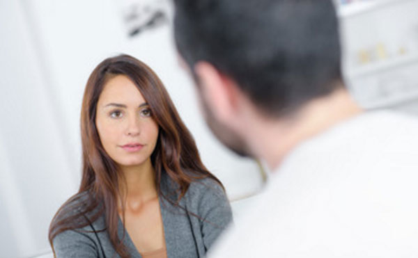 Женщина общается с мужчиной, слегка улыбается