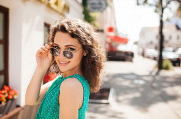 Девушка приспустила солнцезащитные очки. Строит глазки и улыбается