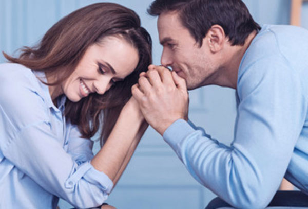 Муж с женой сидят друг напротив друга. Мужчина целует руки женщины, она смущается
