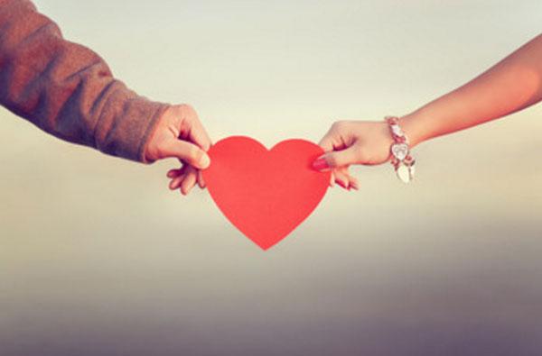 Женская и мужская рука с разных сторон держатся за бумажное сердце