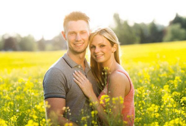 Счастливая пара на поляне с цветами