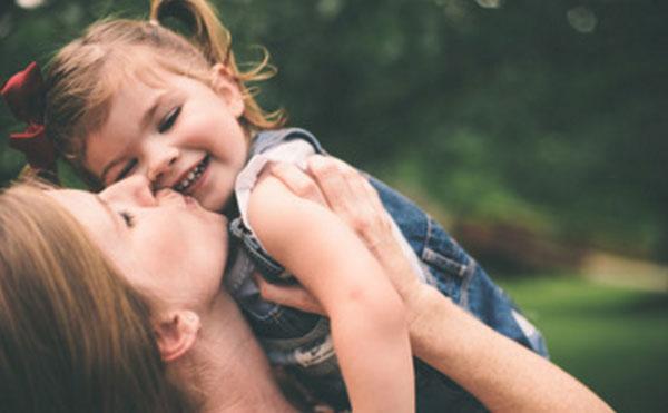 Мама целует дочку, которую держит на руках