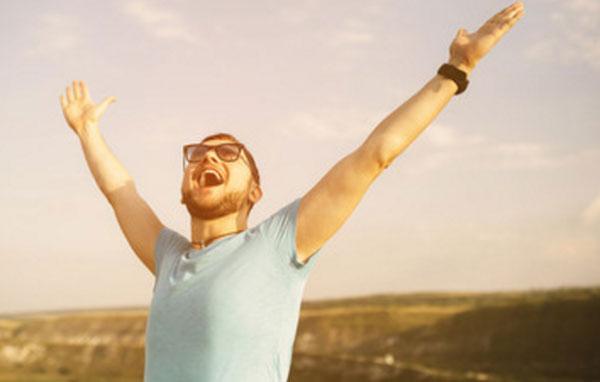 Счастливый мужчина в очках кричит от счастья. стоя на возвышенности