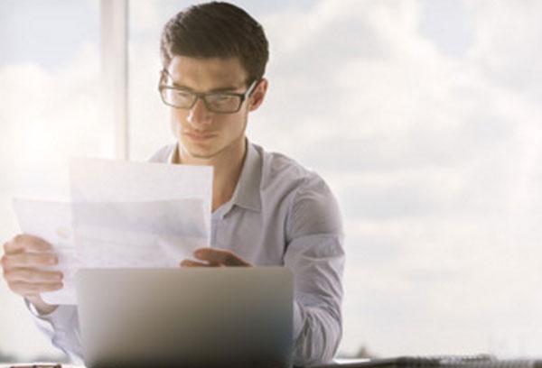 Мужчина в очках сидит перед ноутбуком, рассматривает листки бумаги