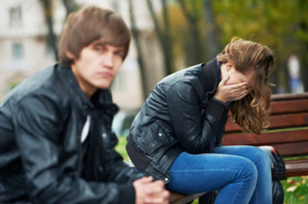 Парень и девушка сидят на скамейке. Она плачет, он серьезен