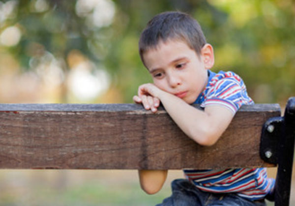 Одинокий грустный мальчик сидит на скамейке