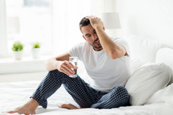Мужчина сидит на кровати со стаканом воды и держится за голову