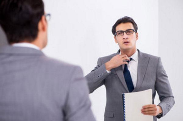 Мужчина в очках с докладом в руке стоит перед зеркалом и поправляет свой галстук от волнения