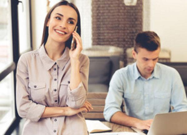 Парень сидит работает за ноутбуком. Девушка стоит рядом с ним и говорит по телефону