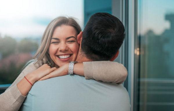 Мужчина стоит спиной. Его крепко обнимает сильно улыбающаяся девушка