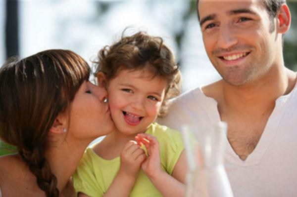Счастливая семья. Женщина целует ребенка в щечку