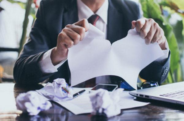 Мужчина в костюме рвет листы бумаги и комкает их