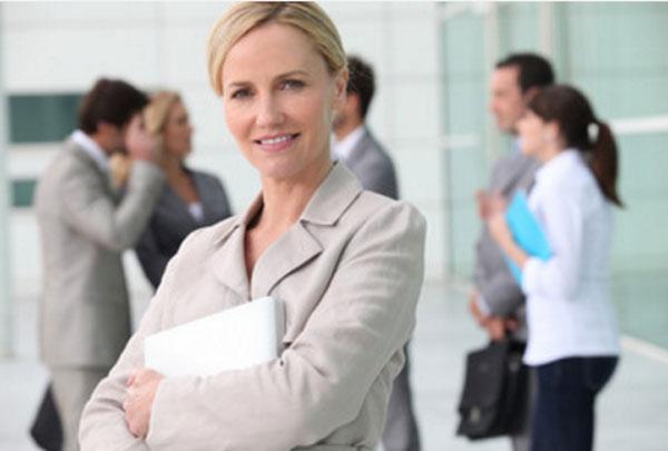 Женщина в костюме улыбается. В руках у нее доклад, сзади стоят люди