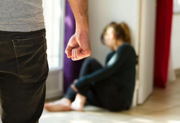 Мужчина с сжатой в кулак рукой приближается к женщине, которая сидит на полу под стеной