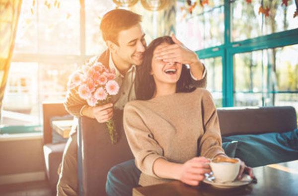 Девушка сидит в кафе с чашкой чая. Сзади подкрался парень с букетом цветов