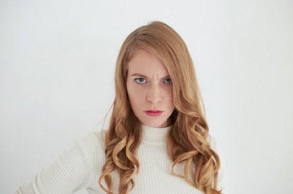 Женщина с серьезным, слегка разгневанным выражением лица