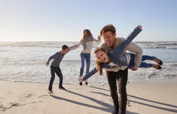 Семья веселиться на берегу моря
