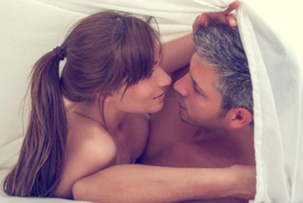 Женщина с мужчиной лежат под простыней
