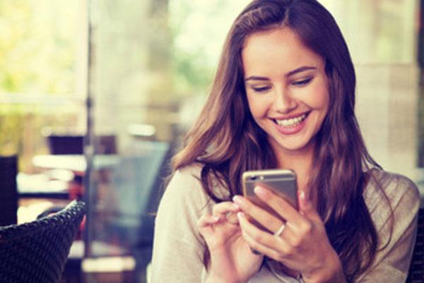 Улыбающаяся девушка набирает сообщение на смартфоне