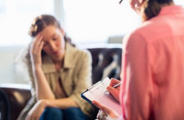 Психотерапевт общается с женщиной