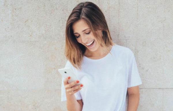 Девушка читает сообщение на телефоне и смеется