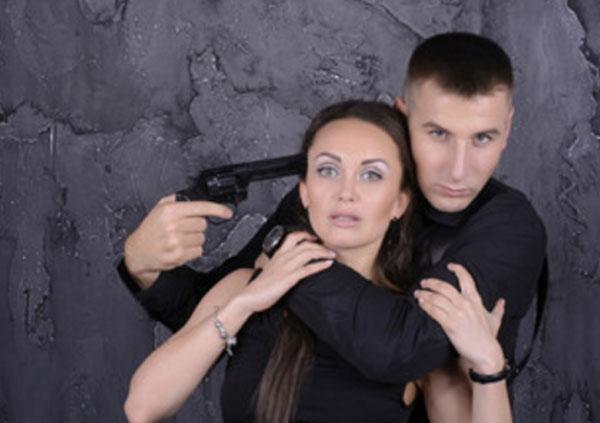 Мужчина схватил женщину, угрожает ей оружеем