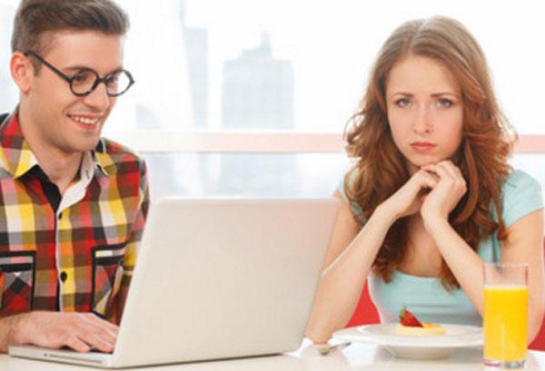 Расстроенная девушка сидит рядом с мужчиной в очках, который увлечен своим ноутбуком
