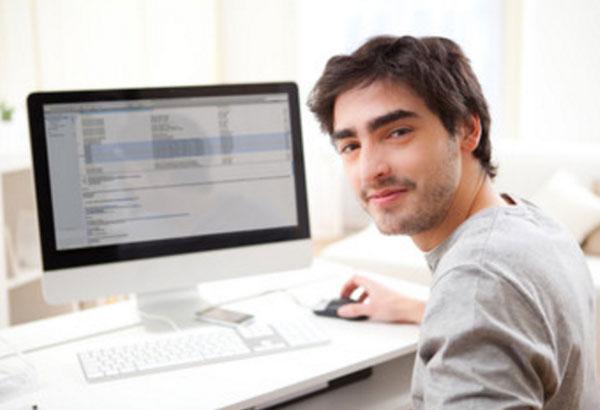 Мужчина работает дома, сидит за компьютером
