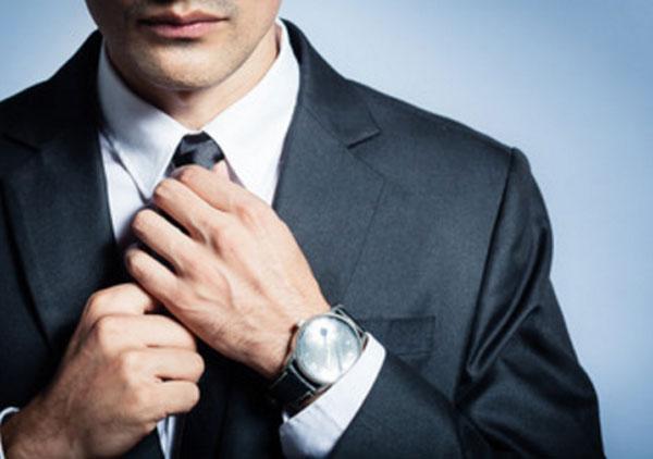 Мужчина в костюме поправляет галстук. Его лицо почти не видно, только губы