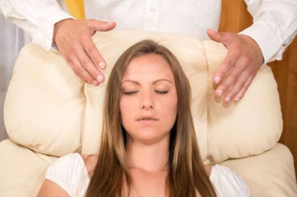 Женщина сидит на мягком кресле. Над ее головой руки гипнотизера