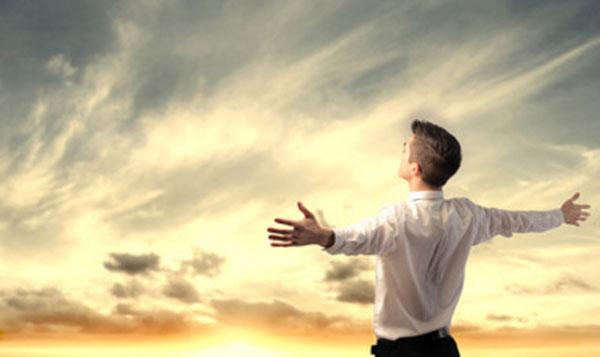 Мужчина стоит спиной, смотрит на небо, у него распростертые руки