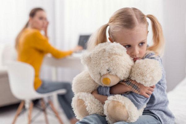 Обиженная девочка сидит обнимая плюшевого медведя. на заднем плане ее мама сидит за столом