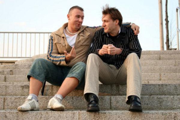 Два мужчины сидят на ступеньках и разговаривают