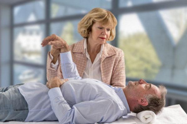 Мужчина неподвижно лежит на кушетке. Рядом стоит женщина, которая держит мужчину за руку