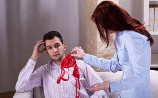 Женщина скандалит с мужчиной, держа в руке красный бюсгалтер