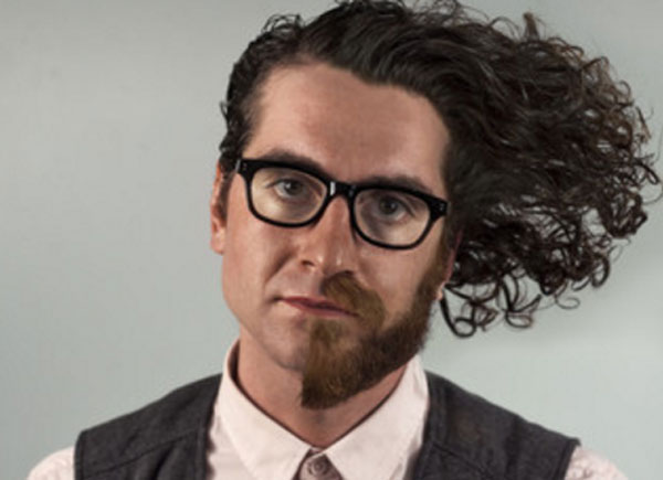Мужчина, лицо которого разделено на половины. Одна с бородой и длинными волосами, другая без бороды и с короткой стрижкой